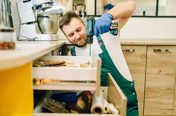 Kitchen fitter fix the kitchen drawer with fitting equipment