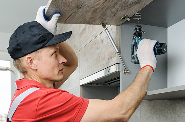 Kitchen Fitter fits the kitchen cabinet with driver
